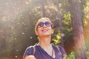 happy woman outdoors looking up at the sky wearing sunglasses in the woods after depression treatment and counseling for depression in Katy, TX 77494