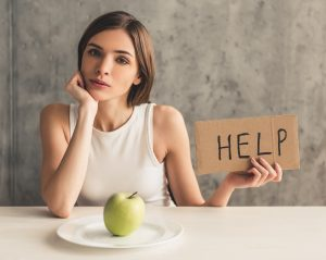 "woman holding a sign that says ""help"" in front of a green apple on the plate before getting help for eating disorder or eating disorder treatment in Katy, TX 77494"