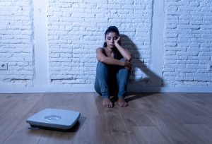 depressed woman looking at the scale because she has anorexia and hasn't gotten eating disorder treatment in Katy, TX 77494
