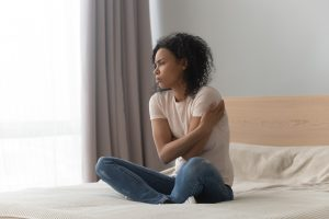depressed woman sitting alone on her bed looking upset before going to Counseling and therapy in Katy, TX 77494 for the symptoms of anxiety