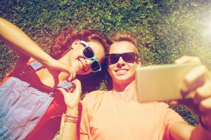happy young couple lays on the grass taking a selfie after going to marriage counseling & couples therapy in katy, tx at the counseling center at cinco ranch near Houston, TX 77494