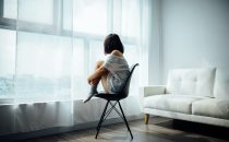 depressed woman sitting in chair by a window