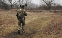 Soldier walking in an open field after receiving help for PTSD
