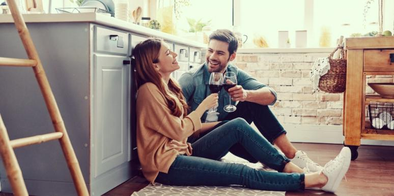 Married couple sitting on the kitchen floor laughing and drinking wine in Katy, TX 77494