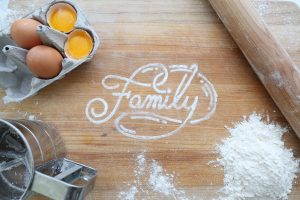 Af family baking together during the pandemic to relieve anxiety and they wrote family in flour on the table