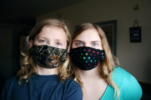 A mother and her young daughter wearing masks and experiencing stress during the pandemic