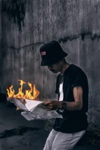 A man holding a newspaper on fire depicting how someone may feel from work burnout