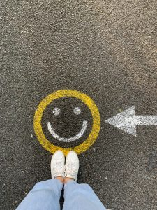 A teenager standing by a smiley face chalk art that she drew after her CBT session to overcome negative thinking