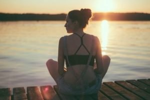 A woman sitting on a dock at the lake incorporating mindfulness techniques she learned during therapy in Katy, TX 77494