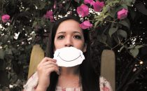 A girl holding a smiling face in front of her own face to mask her pain from self-harm
