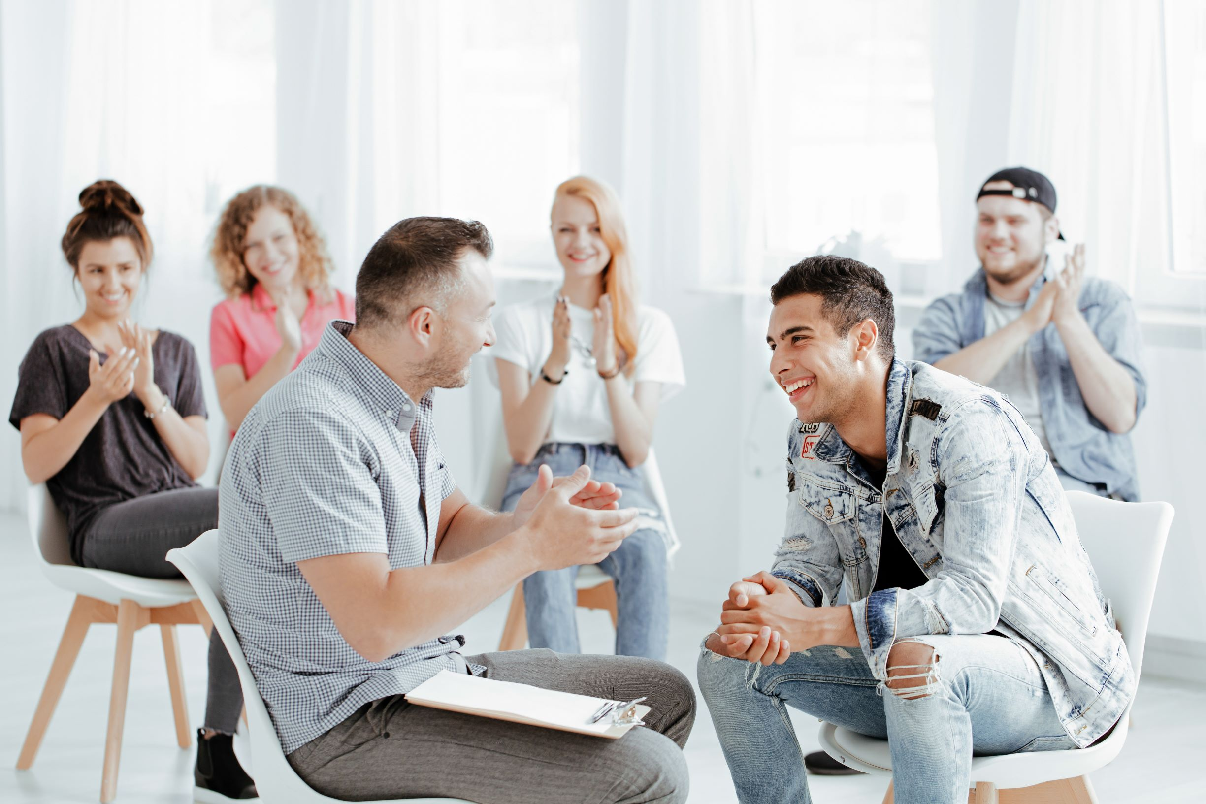 A teen group therapy session occurring in Katy, TX 77494 discussing issues such as anxiety and depression treatment. Group of people sitting in a circle clapping for an individual. Represents group therapy and how group therapy for teens can help teens.