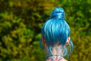 A teen girl with blue hair walking outside. Represents the need for parenting teens in Katy, TX 77494. Represents the need for therapy for teens and family therapy in Katy, TX 77494