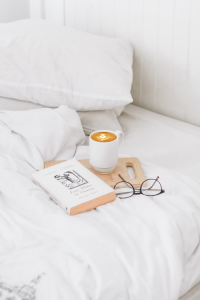 A book and cup of coffee on a bed that represents the need to handle stress and maintain self-care.