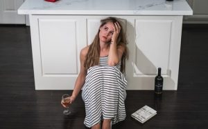 A woman sitting on the floor drinking wine. After her therapy session in Katy, TX she recognizes that she does not handle stress in a healthy way. She is also trying to figure out what causes her stress.