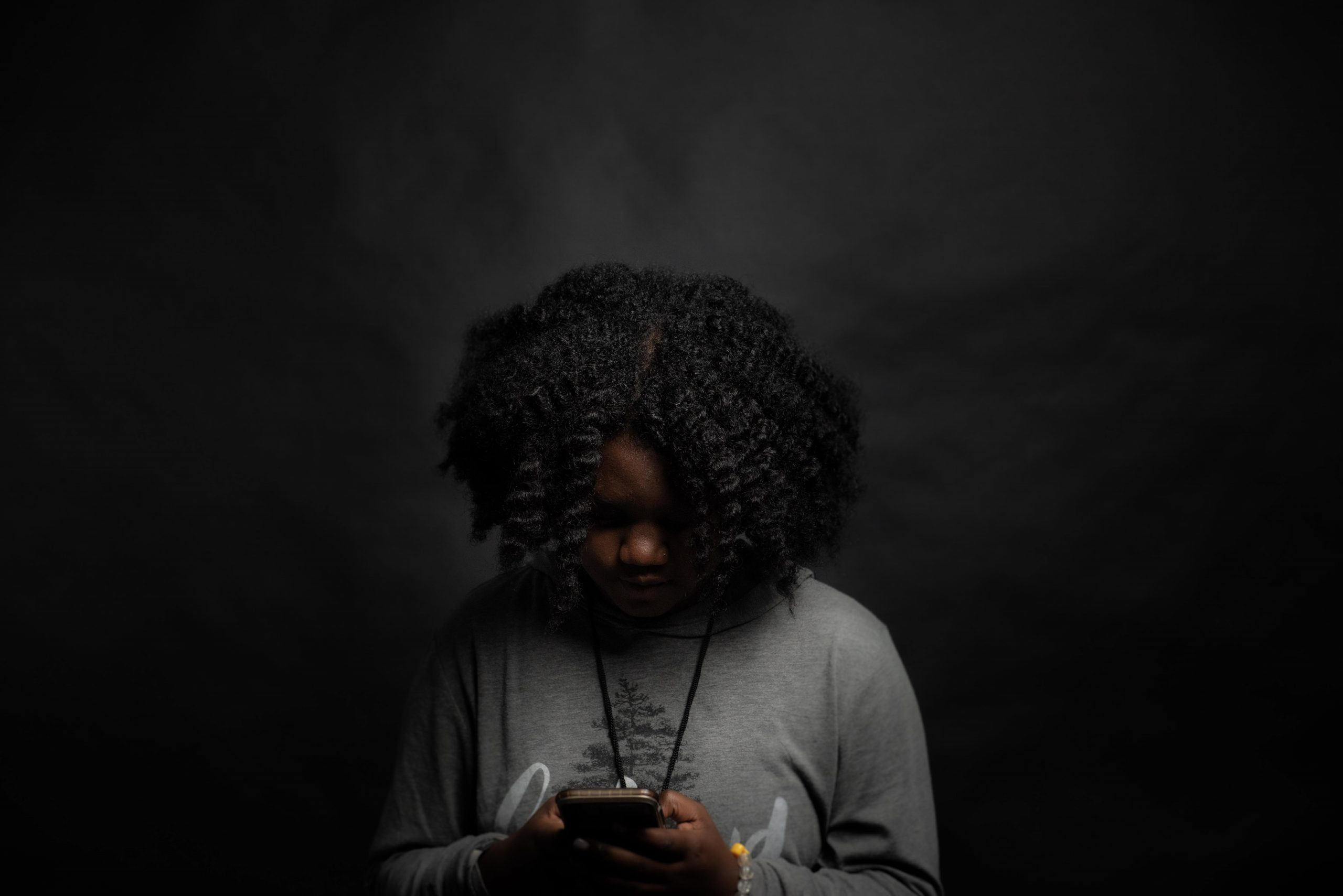 An African American female teen looking at her phone after she has been cyberbullied. Represents the need for teen therapy in Katy, TX 77494