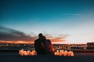A couple sitting looking at the sunset surrounded by candles. Represents the need for couples therapy to resolve conflict in Katy, TX 77494
