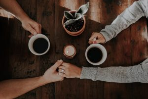 A couple holding hands over a cup of coffee. Represents the need for couples counseling to resolve conflict in Katy, TX 77494