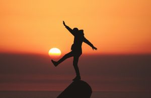 A person standing on a cliff at sunset exploring self care. Represents the need for self-care check and therapy in Katy, TX 77494