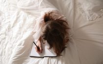 A woman writing in a journal on her bed practicing self-care. Represents the need for a self-care check and therapy in Katy, TX 77494