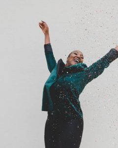 A woman smiling and holding her hands up celebrating her success. Represents the need for counseling to discuss feeling stuck in life in Katy, TX 77494
