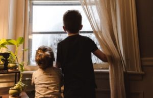 Two small boys staring out the window. They live in a toxic family. Represents the need for therapy in Katy, TX 77494